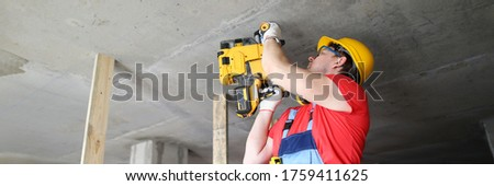 Builder works with special equipment on ceiling. Builder helmet holds heavy tool. Builder works puncher. Mounting guns for concrete are used by professional builders. Driving nails into hard surfaces #1759411625