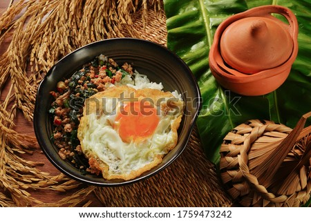 Stir-fried Minced pork with basil and  fried egg or Thai Food Rice topped with stir-fried pork and basil and  fried egg is the popular in Thailand with ancient background, Thai street food. #1759473242