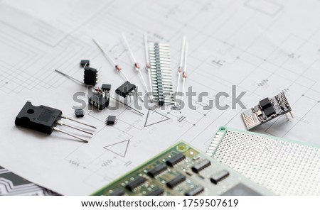 Electronic parts on the background of the schematic diagram. Diodes, microchips, transistors, integrated circuits, capacitors.Design of electronic circuit and electronic Board.Connection diagram Royalty-Free Stock Photo #1759507619