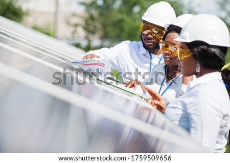 African american technician checks the maintenance of the solar panels. Group of three black engineers meeting at solar station. #1759509656