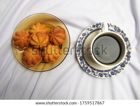 A flatlay picture of Bahulu cake or Malaysian sponge cake with coffee.