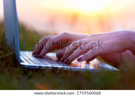 Young woman with laptop resting on green grass in park stock photo