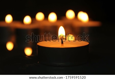 Candle burning in the dark. Candles in the background.