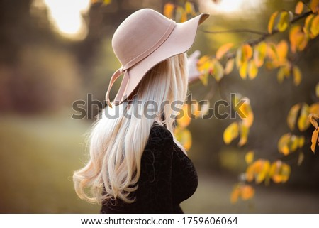 Profile of attractive woman with long blond hair in light pink autumn hat. Copy space. #1759606064