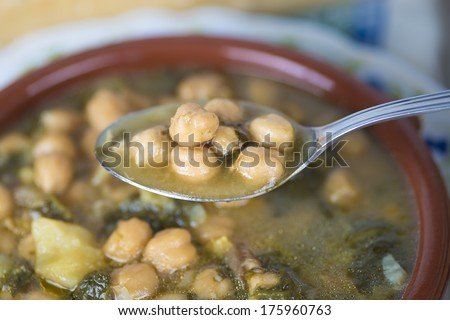 Stew of chickpeas and spinach with cod on a  table with a tablecloth
