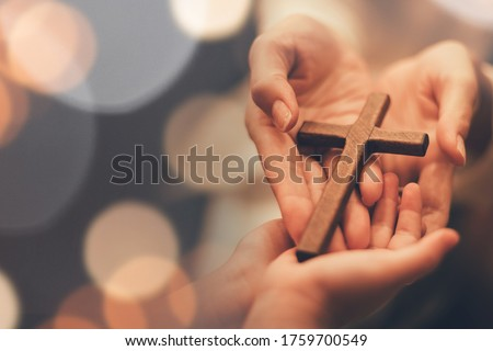 Woman's hand with cross .Concept of hope, faith, christianity, religion, church online. Royalty-Free Stock Photo #1759700549