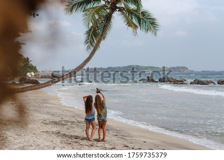Ypung happy tourist women friends taking selfie on the beach, summer vacation concept. Girls taking picture on th phone under palm tree