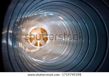 closeup view from inside the galvanized steel air duct on the exhaust fan in the background light, the front and back background is blurred with a bokeh effect #1759749398