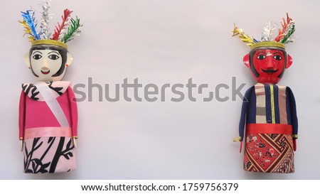 Miniature ondel ondel doll.  To mark it, the male ondel-ondel has a red face, the female ondel-ondel has a white face. This doll comes from the Betawi tribal culture, Indonesia. Copy space for text.  #1759756379