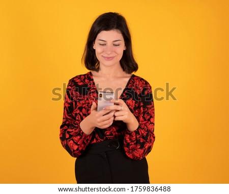 beautiful woman people - woman using smartphone, yellow background