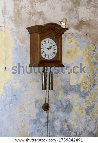 picture with an old wooden clock on the wall in an old castle room