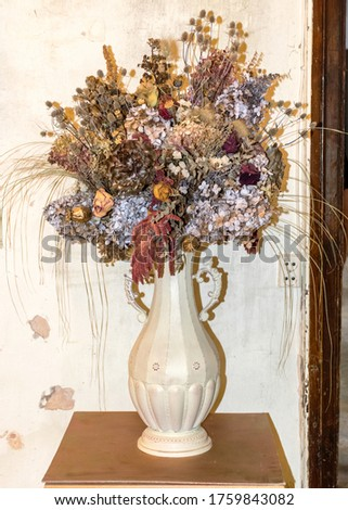 picture with an old vase and dried flowers in an old castle room