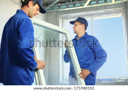 Two workers in blue work clothes set a new window in the window frame #175988183