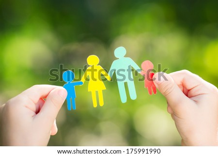 Paper family in hands against spring green background