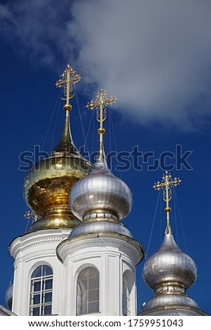 The domes are gold and silver with Orthodox crosses against a blue sky on a bright day, close-up. Old traditional architecture of Russia #1759951043