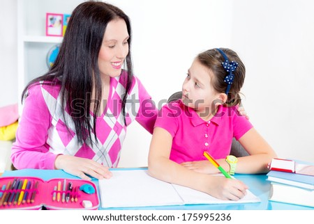 A mother helping her daughter with homework. #175995236