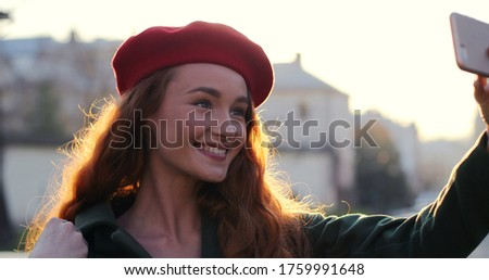 Pretty red-hair young woman smiling, waving a hand and blowing kisses taking a selfie picture on the smartphone camera outside in the sunlight at fall. Close up.