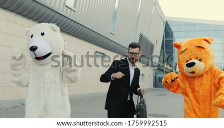 Funny picture of the cheerful Caucasian man in a suit and with a bag in a hand stepping the street and dancing while having fun with two big growth dolls of bears.