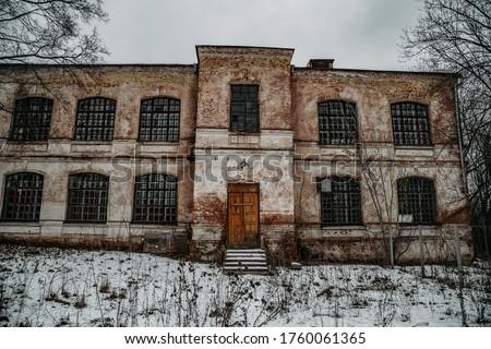 Dark and creepy abandoned haunted mental hospital in winter Royalty-Free Stock Photo #1760061365