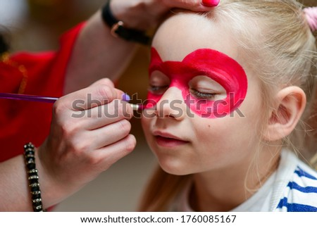 The animator paints the face of the child.