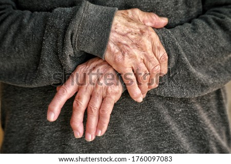 Closeup of old woman arms holding her painful wrist ...arthritis, osteoporosis, rheumatism concept. Numbness of the hand with deformity