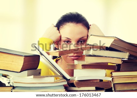 Young woman sitting behind books  #176013467