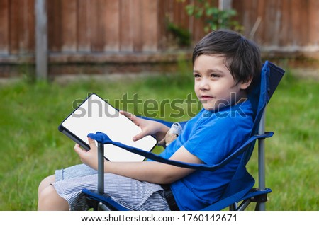 Active kid sitting on chair in the garden playing game or watching cartoons on tablet, Handsome young boy relaxing in the garden on sunny day summer, New normal lifestyle concept