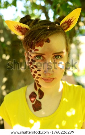 The girl painted her face in the form of a giraffe. African giraffe among the summer foliage. #1760226299