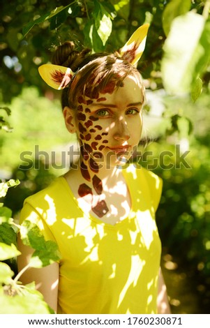 The girl painted her face in the form of a giraffe. African giraffe among the summer foliage. #1760230871