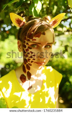 Unusual makeup. Halloween ideas. The girl painted her face in the form of a giraffe. African giraffe among the summer foliage. #1760235884