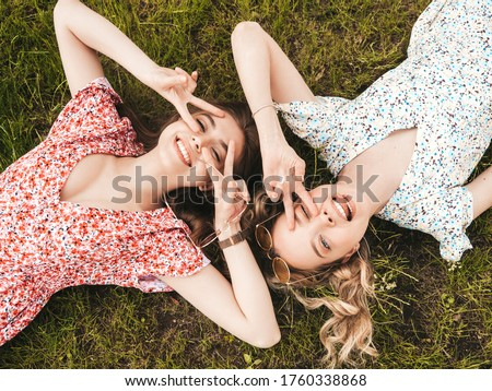 Two young beautiful smiling hipster girls in trendy summer sundress.Sexy carefree women lying on the green grass in sunglasses.Positive models having fun.Top view.They show peace sign Royalty-Free Stock Photo #1760338868