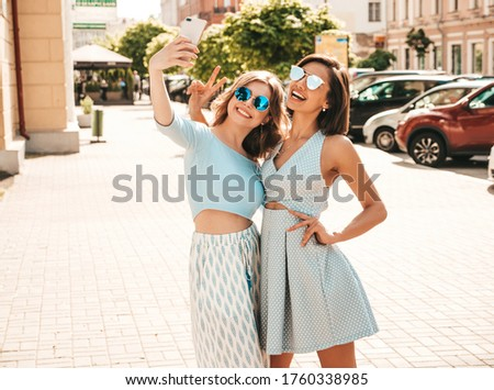 Two young beautiful smiling hipster girls in trendy summer clothes.Sexy carefree women posing on the street background in sunglasses. They taking selfie self portrait photos on smartphone