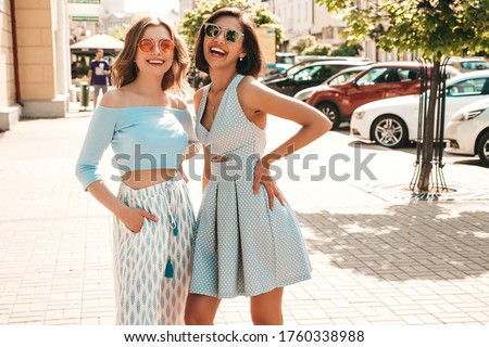 Two young beautiful smiling hipster girls in trendy summer clothes.Sexy carefree women posing on the street background in sunglasses. Positive models having fun and hugging.They going crazy #1760338988