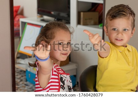 """little brothers make the gesture of """"spiderman"""" with their hands"""