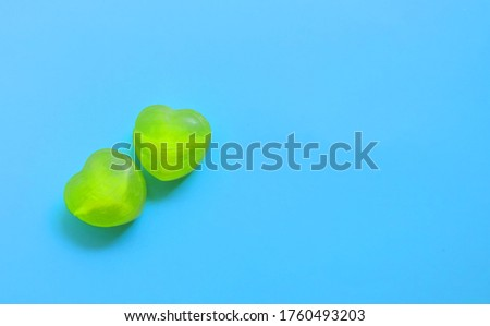 two heart-shaped green lollipops on a blue background,   space for text,  love concept