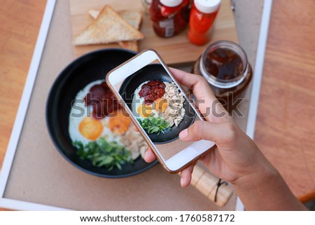 The hand is holding the mobile phone and taking pictures of Indochina pan fried egg with toppings, Chinese sausage and pork sausage in the black pan with flavoring.
