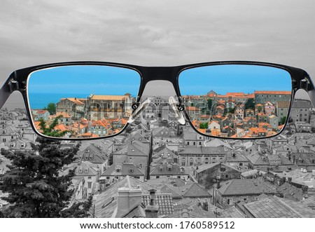 Different perception of world. Colorful view of red roods and blue sea in  the glasses. Looking through glasses.