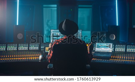 Producer, Audio Engineer Uses Control Desk for Recording New Album Track in Music Record Studio, in the Soundproof Room Musician, Artist, Performer Sings a Song from New Album. Back View Royalty-Free Stock Photo #1760613929