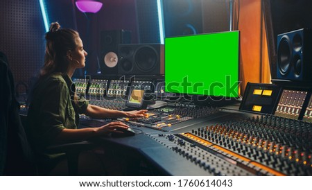 Portrait of Stylish Female Audio Engineer / Producer Working in Music Record Studio, Uses Green Screen Computer, Mixer Board, Control Desk to Create New Song.