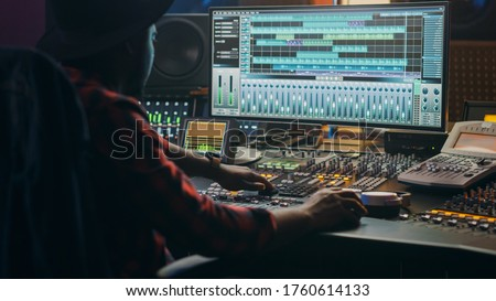 Music Creator, Musician, Artist Works in the Music Record Studio, Uses Surface Control Desk Equalizer Mixer. Buttons, Faders, Sliders to Broadcast, Record, Play Hit Song. Close-up Shot Royalty-Free Stock Photo #1760614133