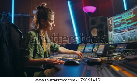 Beautiful, Stylish Female Audio Engineer and Producer Working in Music Recording Studio, Uses Mixing Board and Software to Create Cool Song. Creative Girl Artist Musician Working to Produce New Song #1760614151