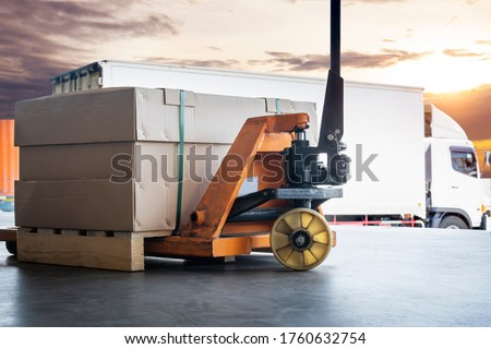 Cargo shipment loading for truck. Large shipments pallet goods with hand pallet truck waiting for load into a truck. Road freight cargo industry. Logistics and transportation. #1760632754