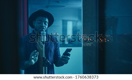 Portrait of Successful Young Black Artist, Singer, Performer Singing His Hit Song for the New Album. Wearing Stylish Hat, Holding Smartphone and Standing in Music Record Studio Soundproof Room. Royalty-Free Stock Photo #1760638373