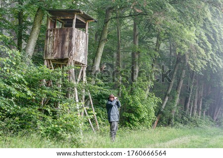 On a foggy, rainy day, a hunter stands in front of his huting pulpit at the edge of the forest and watches his hunting area through binoculars. Royalty-Free Stock Photo #1760666564