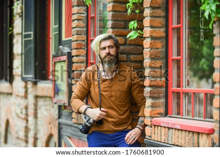 waiting for you. bearded man hipster take photo. photo shooting outdoor. brutal man traveler with retro camera. photography in modern life. travel tips. professional photographer use vintage camera.
