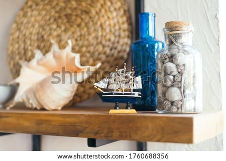Decor on kitchen shelves.  Ship. Marine theme. Bright interior of the kitchen.  Shell.  nautical decor Royalty-Free Stock Photo #1760688356