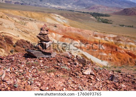 Stone cairn on the red earth in the mountains. Mars valley in the Altai mountains #1760693765