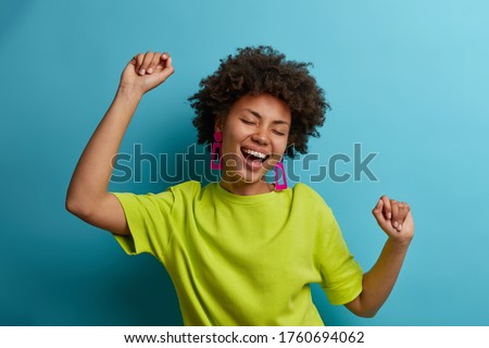 I am winner! Ecstatic overjoyed African American woman dances carefree, celebrates victory and success, dressed in green casual t shirt, feels lively and energetic, isolated on blue background #1760694062