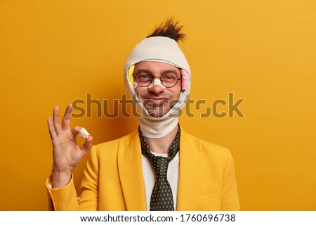 Dont worry, everything is okay. Smiling positive adult man forgets about accident consequences and injuries, gestures ok sign, received first aid from doctor, wears elegant suit, bandage on head #1760696738