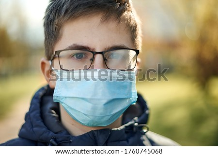Difficulty of entering the mask fog up the glasses. Guy in a medical mask and glasses outdoors. Royalty-Free Stock Photo #1760745068